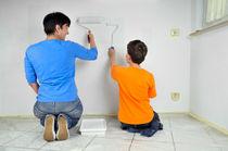 Frau und Kind streichen Wand - Malerarbeiten im Teamwork by Matthias Hauser