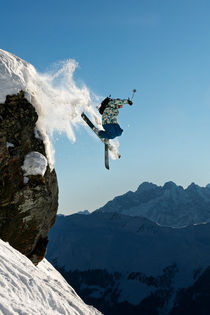 Skier jumping off a rock. by Ross Woodhall