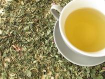 Eine Tasse Tee auf einer Kräuterteemischung by Heike Rau