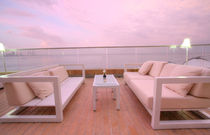 Stunning view of outdoor chairs and a couch to enjoy the sunset of the beach by David Castillo Dominici