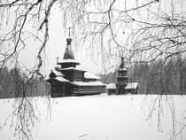 The ancient wooden temple in snow is visible through branches of trees by Roman Popov