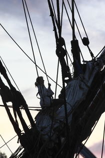 Young woman climbing in the rigging of a tall ship at dusk by Intensivelight Panorama-Edition