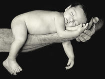 Baby in father's arms peacefully sleeping by Söndra Rymer