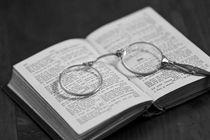 Brille liegt in aufgeschlagenem alten Buch by Kurt Gruhlke