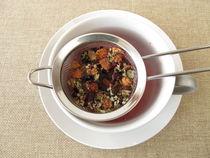 Kräutertee mit Früchten und Blüten im Teesieb by Heike Rau