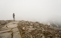 Person standing in fog on peak von Arletta Cwalina