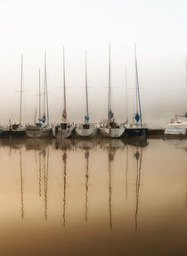 Boats moored to bridge in foggy weather by Arletta Cwalina