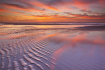 Beautiful sunset and reflections on the beach at low tide by Sara Winter