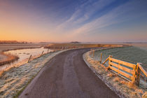 Typical Dutch landscape with a dike, in winter at sunrise von Sara Winter