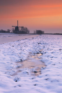Typical Dutch landscape with windmill in winter at sunrise von Sara Winter