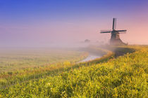 Traditional Dutch windmill at sunrise on a foggy morning von Sara Winter