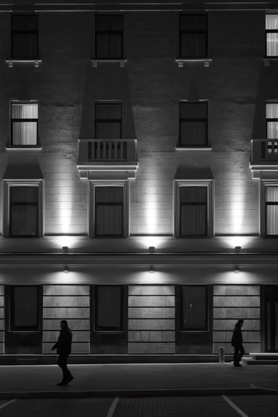 Exterior-building-facade-at-night-with-people-walking