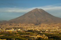 Single volcano on the background of the city at sunset. by Aleksei Diachkov