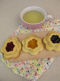 Mit Marmelade gefüllte Blümchenkekse und Tee auf einem Häkeldeckchen by Heike Rau