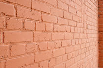 Angle view of a brick wall with a layer of red paint by Vladislav Romensky