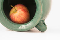 close up view of a red apple inside the greenish earthen jar by Masoud Rezaeipoor