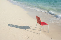 An Empty Single Red Chair at Beach With Shadow by Masoud Rezaeipoor
