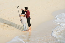 loving couple taking self-portrait on beach by Masoud Rezaeipoor