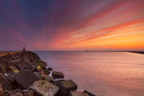 Sunset over harbour entrance at sea in IJmuiden, The Netherlands by Sara Winter
