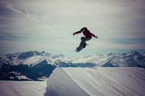 Snowboarder springt vor gewaltiger Bergkulisse by Jochen Conrad
