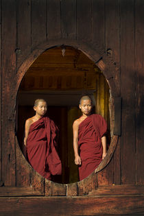 Two young buddhist monks at a wooden window in Myanmar von nilaya