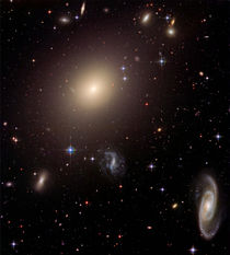Elliptical Galaxy and its Host Galaxy Cluster. by Stocktrek Images