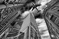 A jet plane flying over the city by Bombaert Patrick