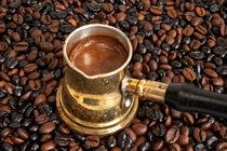 Foaming coffee in an arab copper coffee pot by kgm