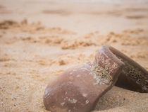 Discover a brown broken and destroyed ceramic vessel on the beach after storm. by nese