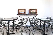 Ein Arrangement von Tischen und Stühlen und zwei alten Radios von Gina Koch