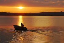 fisherman with motorboat at the lake in sunrise by Christian Zirsky