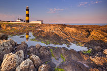 Lighthouse in Northern Ireland at sunset by Sara Winter