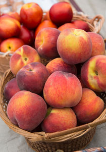 Fresh Peaches in a wicker basket by Michael Moriarty