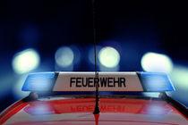 Feuerwehr Auto fährt im Dunkeln mit Blaulicht von fotowelt-luebeck