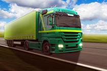 Grüner LKW fährt auf der Landstraße von fotowelt-luebeck