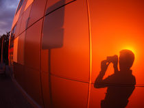 The shadow of a man on a red-orange wall, who photographs a road sign von Vladislav Romensky