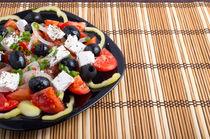 Fresh vegetarian salad in a black plate on a bamboo mat closeup by Vladislav Romensky