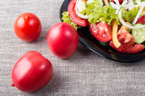 Close-Up top view on fresh tomatoes and a bowl of vegetarian salad by Vladislav Romensky