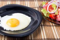 Fried eggs with yolk on a black plate and a salad von Vladislav Romensky