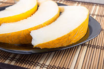 Slices of juicy yellow melon on a black plate closeup by Vladislav Romensky