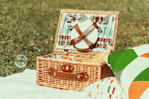 Picnic Basket Food On White Blanket With Pillows And Soap Bubbles by Radu Bercan