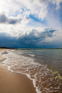 Cloudy sky over a wavy beach by Jessy Libik
