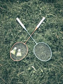 Badminton Racket And Shuttlecock Equipment In Grass by Radu Bercan