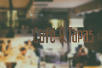 Cafe And Tapas Restaurant Sign With Blurred People Background by Radu Bercan