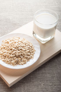 Plate with dry cereal and a glass of milk by Vladislav Romensky