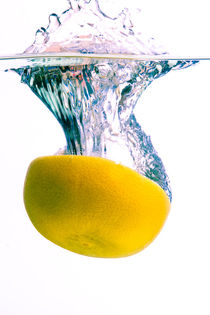 Grapefruit falls into water with big splash on white background von Sharon Yanai