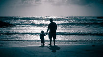 Father and Son on the beach at dusk by Sharon Yanai