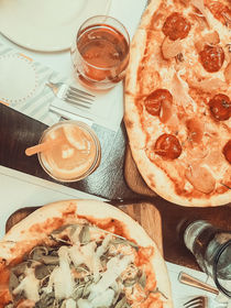 Pizza And Lemonade Juice On Table by Radu Bercan