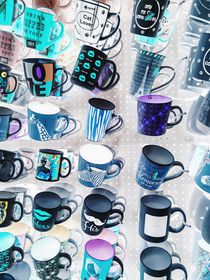 colorful mugs hanging on the white wall von timla
