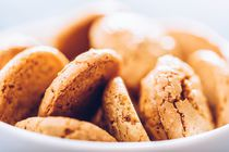 Italian Amaretti Biscuits In White Bowl by Radu Bercan